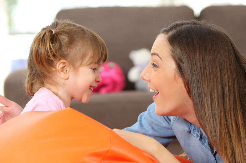 mother laughing and talking to her young girl child