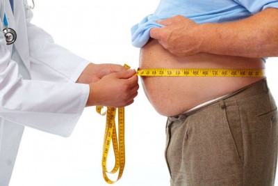 Doctor measuring obese man waist body fat