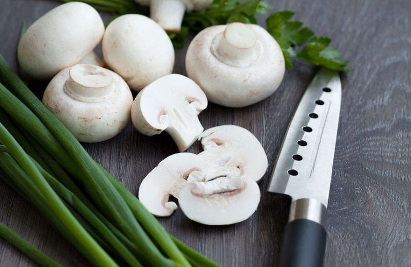 Fresh white button mushrooms on a wooden background