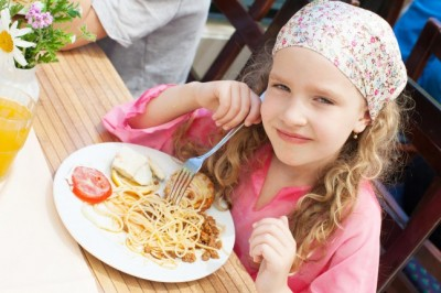 Girl Child eating pasta at cafe