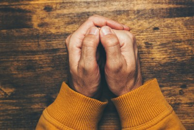 view of religious male crossed hands in prayer