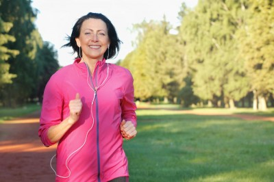 woman running in the park with headphones on