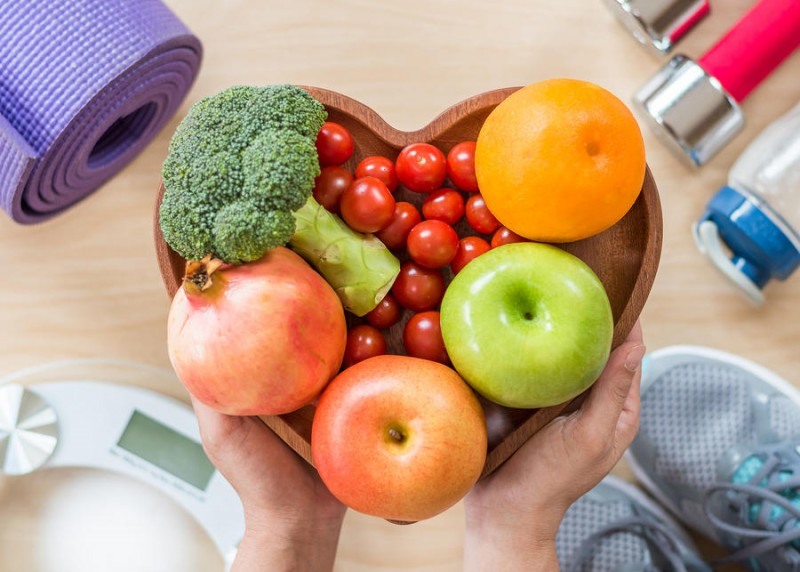 fresh vegetables and fruits in a wooden heart shaped dish with exercise equipment and weighing scale in the background