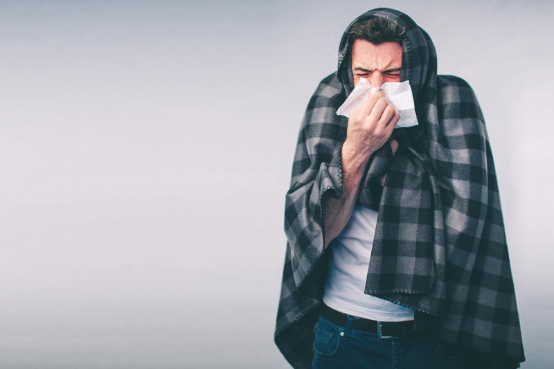 young man blowing his nose and covered with a blanket