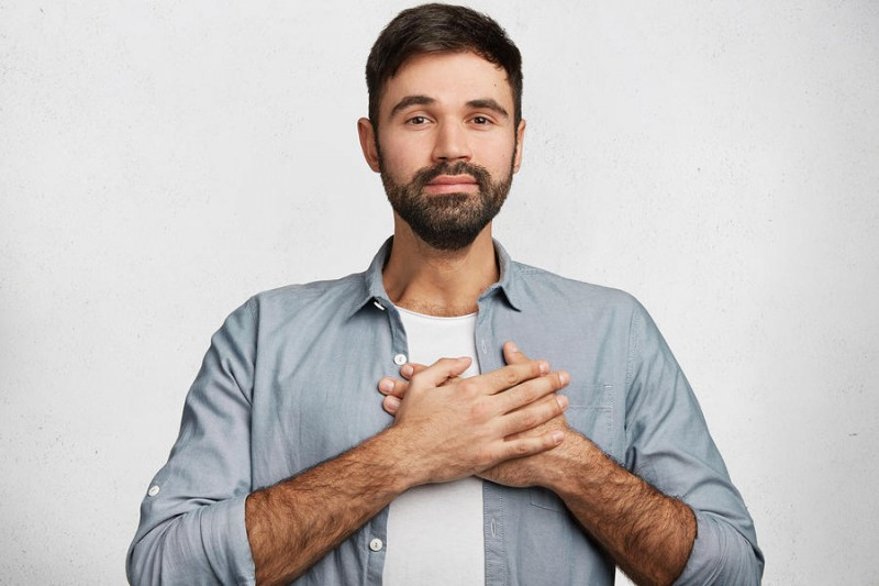 beared man with his hand on his heart, smiling
