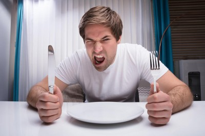 Angry Man Holding Knife And Fork With Empty Plate On Table