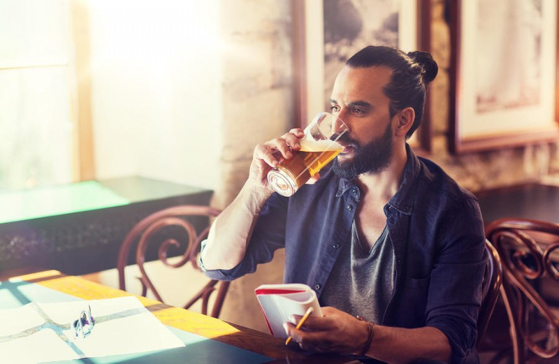 happy young man with notebook drinking beer at bar or pub