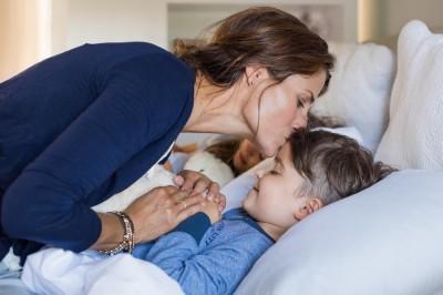 Mother giving good night kiss to sleeping son