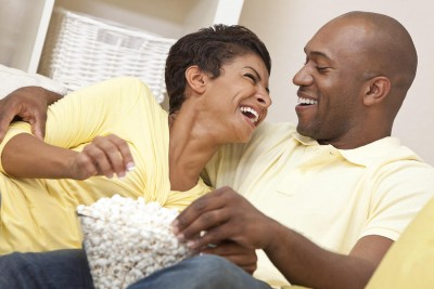 Save Download Preview A happy African American man and woman couple in their thirties sitting and laughing eating popcorn