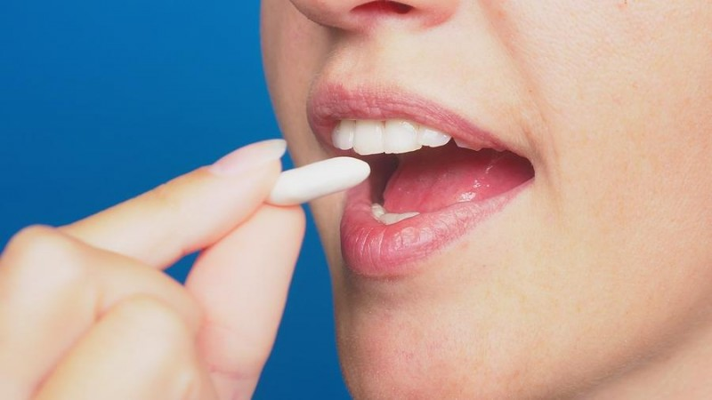 close up of woman putting chewing gum in her mouth