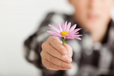 boy offering a piink flower