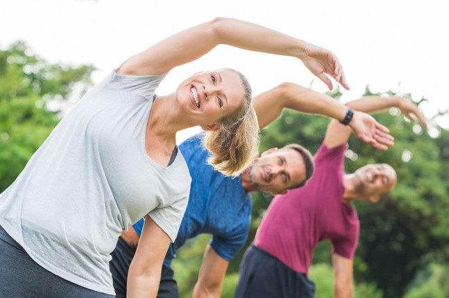 mature healthy people doing stretching at park.