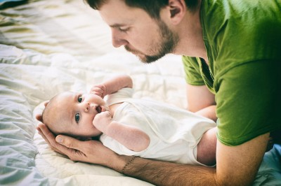 father and holdin baby on white bed