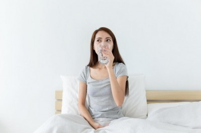 Save Download Preview Asian woman drinking a glass of water while sitting on a bed