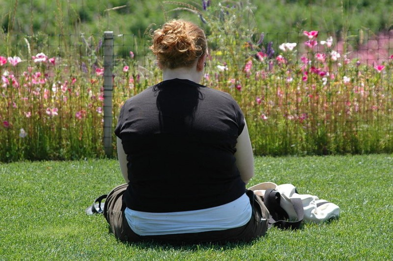 overweight woman sitting in a garden with back facing
