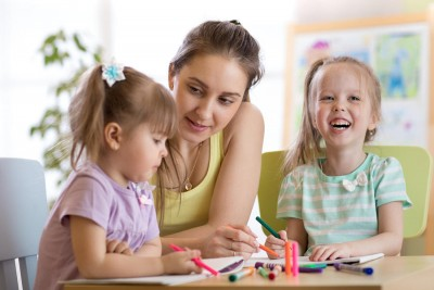 Teacher sitting at desk with two preschooler children