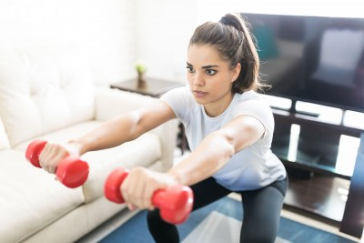 woman doing squats with weights in hand at home