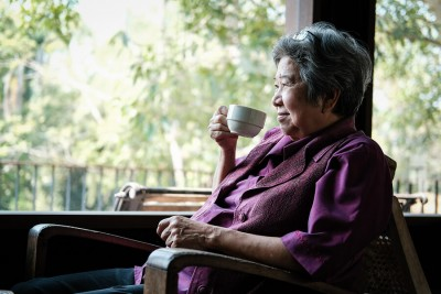 asian elder woman holding tea cup on terrace