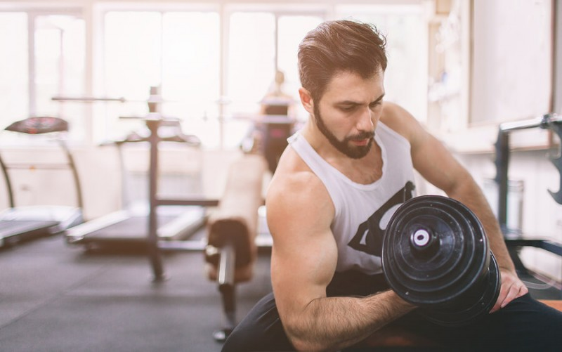 bearded man working out with dumbells in the gym