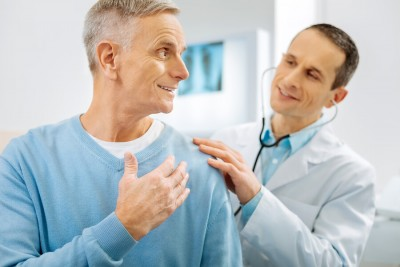 cheerful optismistic man turning to his doctor while being checked up