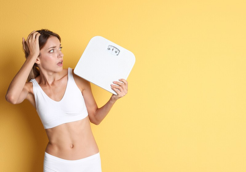 Worried young woman holding bathroom scales