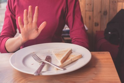 woman saying no to toast on her plate