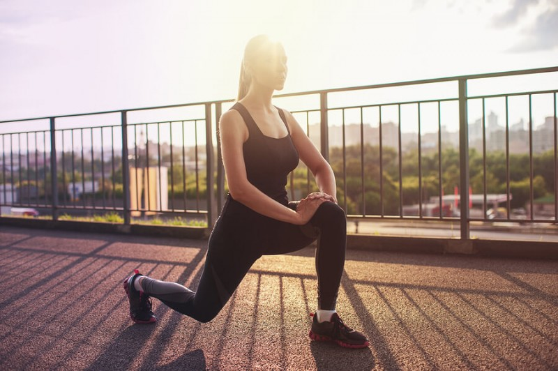 a woman doing evening exercise outdoor as the sun sets