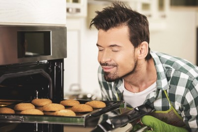 smiling man sniffing baked cookies from an oven