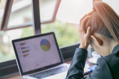 stressed woman at work with hands on her head while looking at the laptop