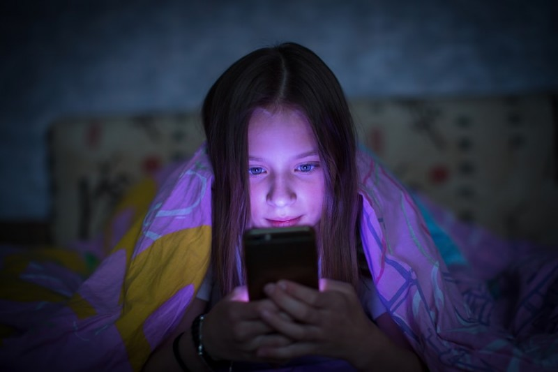 Teen girl lying in bed at night and looking at the glowing screen of smartphone.