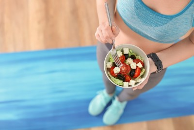 woman in athletic clothes holding a bowl of salad