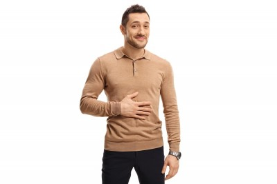 smiling man with one hand on his stomach