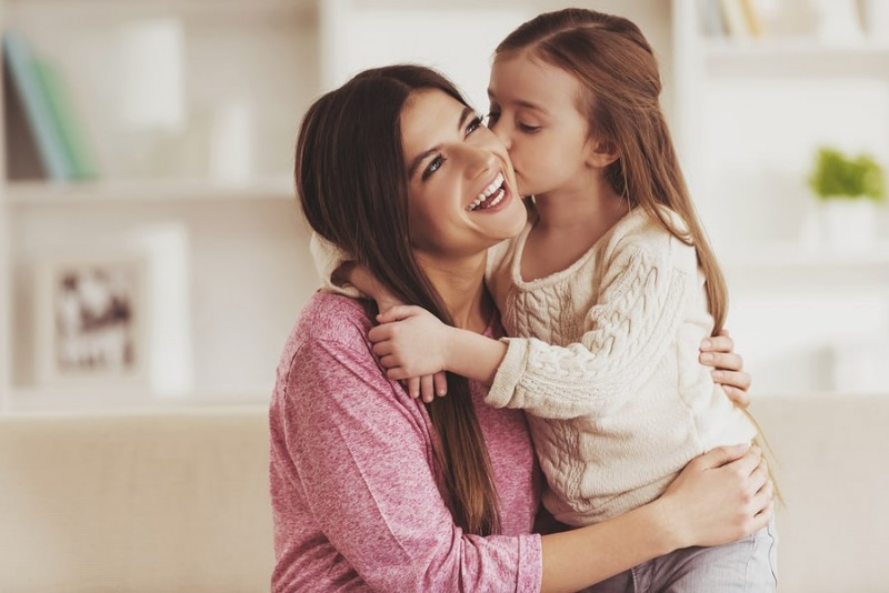 young daughter hugging and kissing her smiling mother