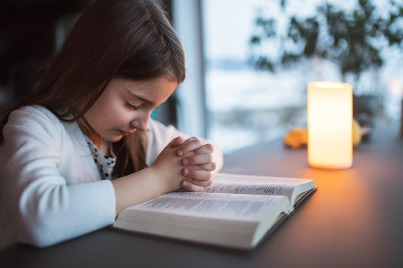 a small girl with the bible praying