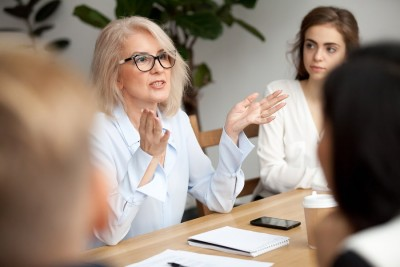 female leader or mentor talking to other employees
