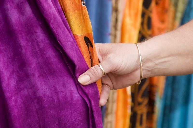 woman's hand touching purple fabric