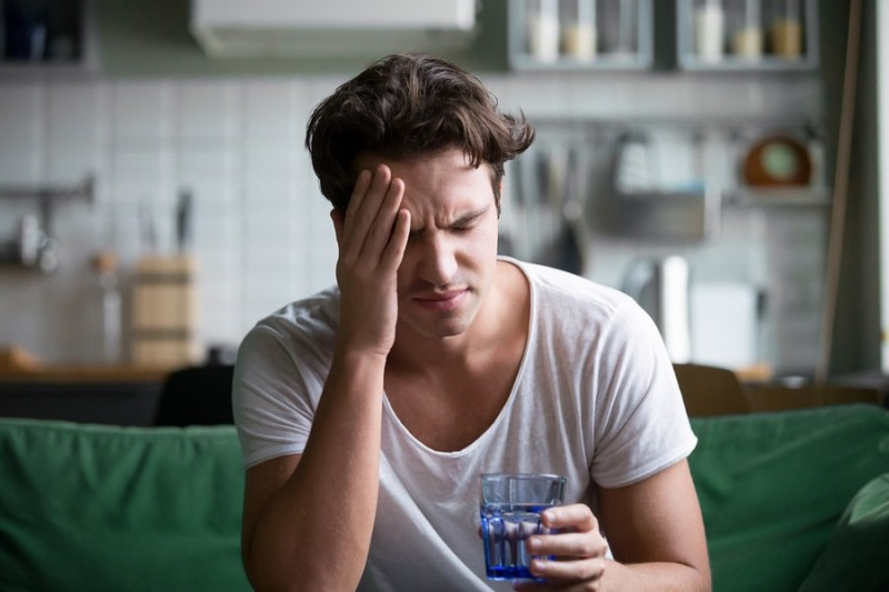 young man touching his head in pain with a glass of water in other hand