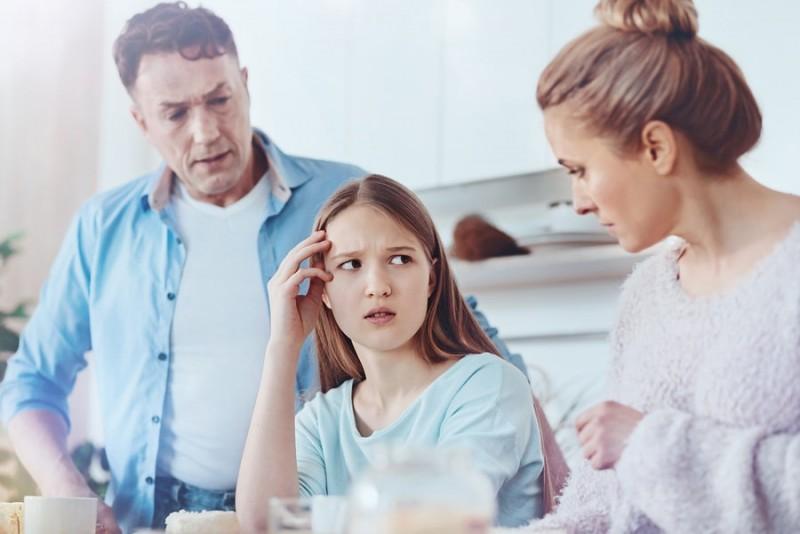 pareparents talking to the teenage daugher who looks upset