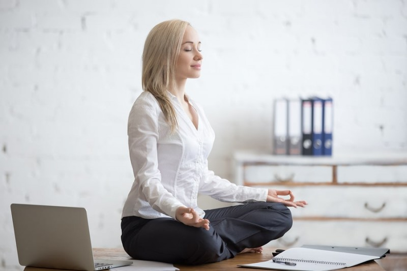 female entrepreneur sitting corss legged on a desk meditating