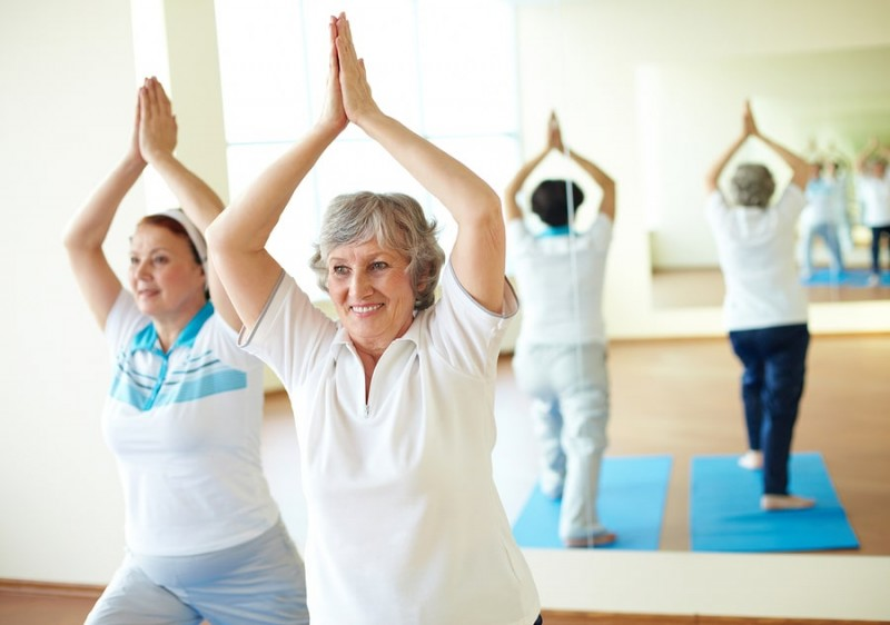 two aged females doing yoga exercise in sport gym